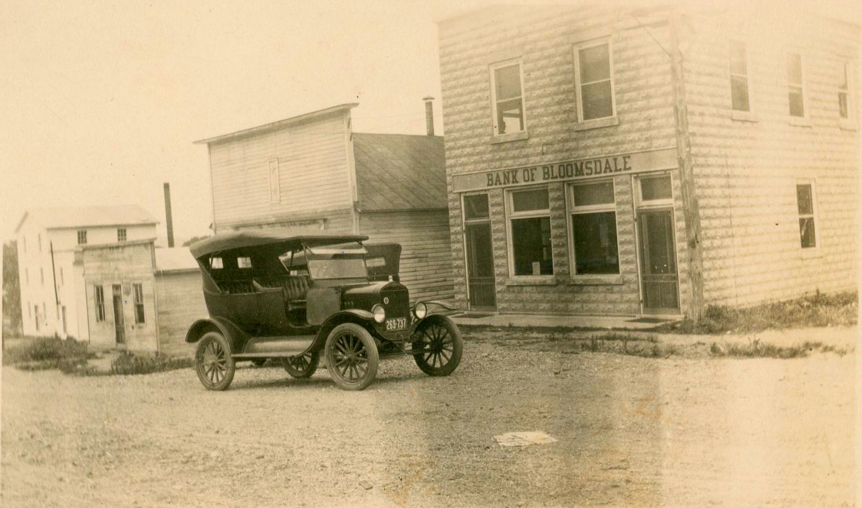 old photo of Model T in front of Bank of Bloomsdale